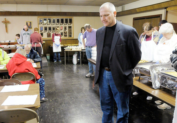 Don Knight / The Herald Bulletin<br /> Christian Center Executive Director Neal Kirby prays over the Center's Thanksgiving Dinner at the Knights of Columbus on Thursday.