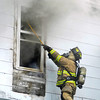 This fireman ventilates the second story of this house at 832 West Second Street as Anderson firefighters battle a blaze that broke out about 5 p.m. Tuesday afternoon.  No one was home at the time of the fire and no one was hurt.