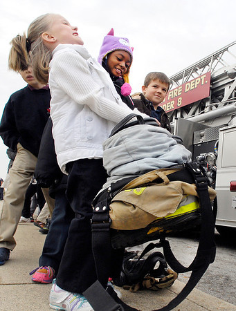 Valley Grove Elementary School first grader Jocelin Everman strains to lift the boots and turnout gear of a Anderson firefighter as classmates Urriah Greene and Harrison Stockwell look on. Anderson's Ladder 8 & Medic 3 were at the school Tuesday morning to give the first graders a fire safety program that was postponed from last week due to weather.<br /> <br /> <br /> <br /> AFD Ladder 8 & Medic 3 at Valley Grove Elementary School for fire program.