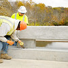 Don Knight/The Herald Bulletin<br /> From left, Kelley Kelly and Paul Storms Sr. with the Schutt-Lookabill Company use chisels to clean up the railing on the County Road 600 West bridge over the White River on Friday. The railing design is not commonly used but is historically accurate to the bridge. The Madison County Commissioners John Richwind, Steffanie Owens and Jeff Hardin took part in a ribbon cutting at the bridge on Friday. The span will be sealed on Saturday and if all goes well will open to traffic by noon Sunday.