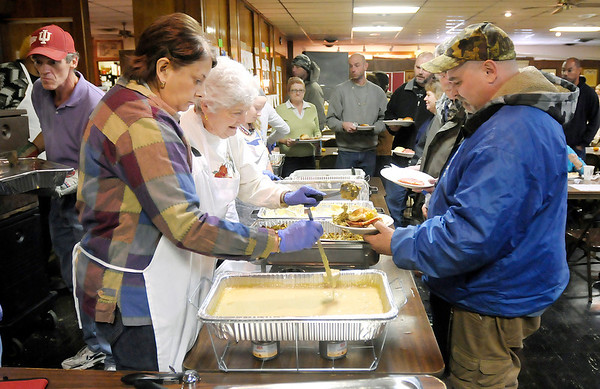 Don Knight / The Herald Bulletin<br /> From left, Nancy and Sara Vargo add stuffing and gravy to Mike Jackson's plate during the Christian Center's Thanksgiving Dinner at the Knights of Columbus on Thursday.