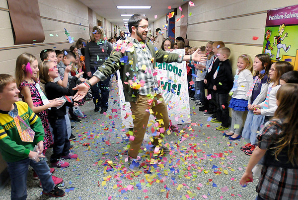 Don Knight/The Herald Bulletin<br /> Students toss confetti at Pendleton Elementary School Assistant Principal Matt Davis as he parades through the hallways as students and teachers congratulate him Wednesday morning for being named Assistant Principal of the Year for Indiana.