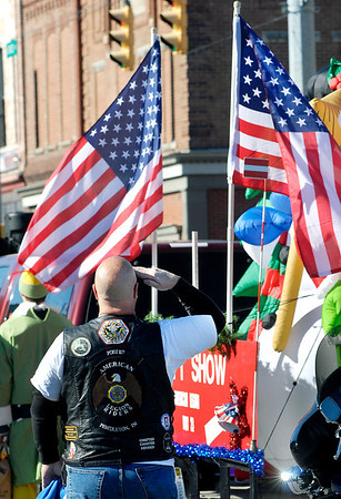 Members of the Pendleton Post 117 American Legion Riders salute the American flag as the national anthem is played at the start of the Christmas in Pendleton parade Saturday.