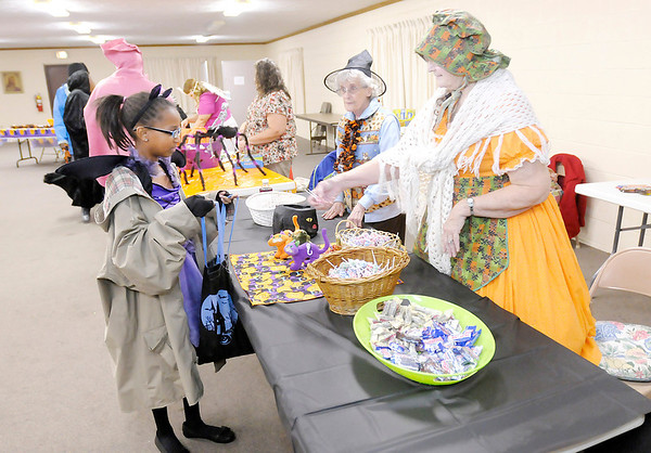 Don Knight/The Herald Bulletin<br /> Mary Borders gives Jade Peeples some candy as Dawn Rousey looks on at New Life Church of the Nazarene on Thursday. The church's Trunk and Treat event was moved indoors due to the weather.