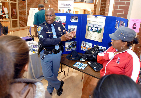 Indiana State Trooper Ray Poole talks to students and parents about the State Police Summer Youth Camps during the Anderson Black Expo Teen Summit Saturday evening.