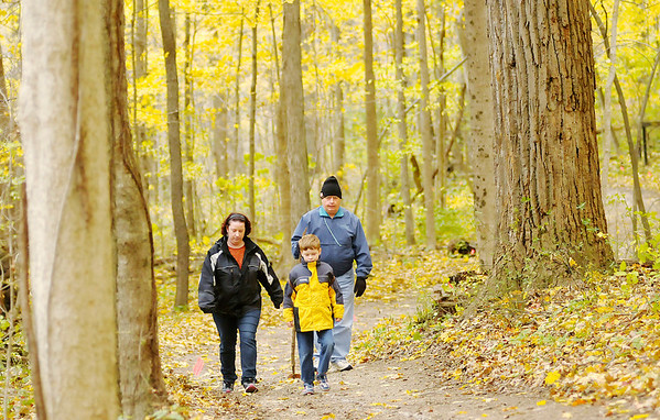 Don Knight/The Herald Bulletin<br /> From left Heather, Peyton and Larry Ramey hike through the woods at Mounds State Park on Saturday. The three generations of Rameys were part of a large family get together to celebrate Thanksgiving.