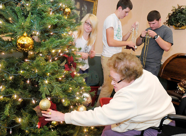 """Don Knight/The Herald Bulletin<br /> Resident Ruth Miller places a poinsettia as she helps volunteers, from left, Emily Reger and brothers Quinton and Weston Bell decorate a Christmas Tree at Bethany Pointe during their """"Hanging of the Greens"""" on Thursday."""