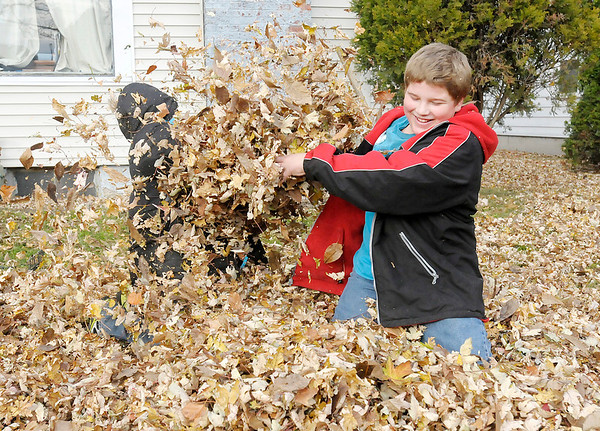 Don Knight/The Herald Bulletin<br /> Brothers Raymond Lee, left, and Kevin Ripberger play in pile of leaves after school on Friday.