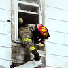 This fireman pulls away siding to get to hot spots from a second story window of this house at 832 West Second Street as Anderson firefighters battle a blaze that broke out about 5 p.m. Tuesday afternoon.  No one was home at the time of the fire and no one was hurt.