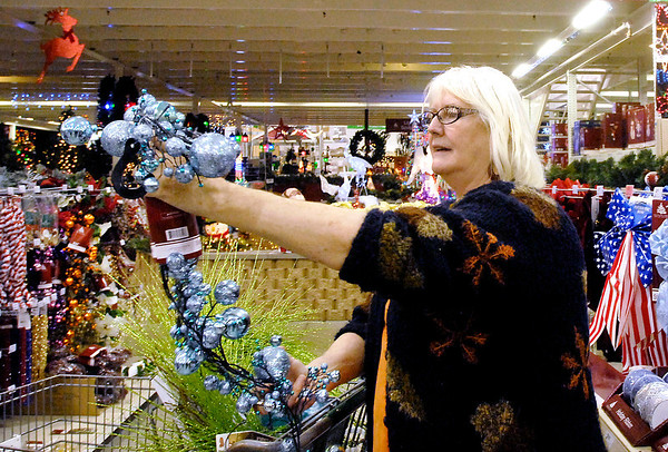 Toni Ward, from New Castle, checks out Christmas items as she shops at Menards in Anderson Thursday.