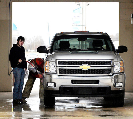 Jake Knobloch, 17, holds the sprayer as his father Jeff Knobloch works to wash off some tacky material that was on the side of his new truck Monday at The Wash Tub car wash on north Broadway.