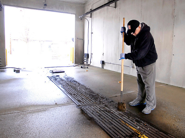 Tom Jewell uses a spade to help clean out the small drain slots in one of the car wash bays at ZALO Kar Wash at Nichol and Madison Avenues Wednesday afternoon.  Jewell and his son had purchased the car wash about a month ago and have been working on making improvements to the facility.