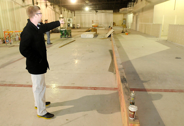 Don Knight/The Herald Bulletin<br /> Alex Baker, a regional manager for Planet Fitness, describes the layout for the companies new Anderson location. Officials say they hope to open before the holidays.