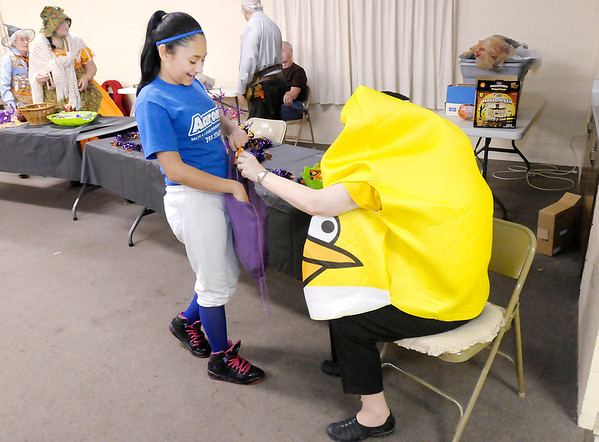 Don Knight/The Herald Bulletin<br /> Dressed as an Angry Bird, Lynda Dayton gives Alexis Arauz candy as trunk and treating was moved indoors at New Life Church of the Nazarene on Thursday. Due to inclement weather Anderson will have trick or treating on Friday.