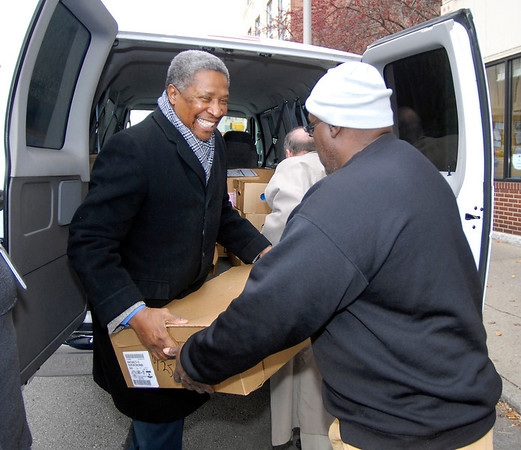Rudy McMillan, director of food and beverage for Hoosier Park, greets a Christian Center volunteer with a case of turkeys as Hoosier Park donated food to the center Tuesday for the Thanksgiving holiday.  Hoosier Park gave the Christian Center 14 cases of turkeys, 9 cases of ham, 19 cases of milk, and 2 cases of eggs for their holiday feast.