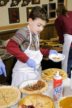 Don Knight / The Herald Bulletin<br /> Madden Pitcock, 9, serves a slice of apple pie while working the dessert table during the Christian Center's Thanksgiving Dinner at the Knights of Columbus on Thursday.