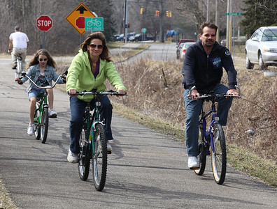 2013_03_10__Emily Hetrick, left, age 12, her mother Janet Hetrick, and her father Ken Hetrick enjoy a bike ride in Oberlin along the Inland Trail bike path. photo by Ray Riedel