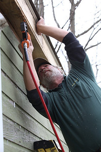 2013_03_10__John Butler fastens the soffits to the new roof he built for the old coal building along the Inland Bike trail in Oberlin on Sunday. photo by Ray Riedel