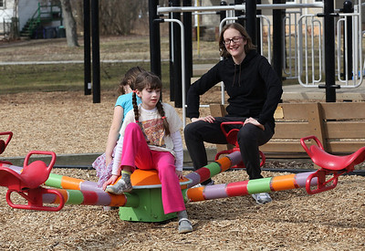 2013_03_10__Zenobia Calhoun, age 7, with Mariana Thomas, age 8  behind her enjoy the teeter totter while watched by Elizabeth Wilmer in the small park at the Oberlin Community Services Center.  photo by Ray Riedel