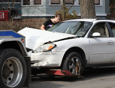 2013_03_10__Caitlin Mehrtens, age 19, Oberlin College student looks into the window of her Ford Taurus before it is towed away. Neither Mehrtens, nor her two passengers were injured after a collision with a Honda Odessey that allegedly ran a stop light at the intersection of E. Lorain and N. Pleasant in Oberlin on Sunday. photo by Ray Riedel