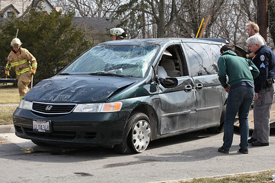 2013_03_10__The driver and an Oberlin Police Sergeant inspect a Honda  Odessey at the corner of E . Lorain and N. Pleasant in Oberlin that was struck by a Ford Taurus after the Honda allegedly failed to stop at a stop light. Despite the severe damage and rollover, the driver was unharmed. photo by Ray Riedel