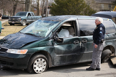 2013_03_10__An Oberlin Police Sergeant inspects a Honda  Odessey at the corner of E . Lorain and N. Pleasant in Oberlin that was struck by a Ford Taurus after the Honda allegedly failed to stop at a stop light. Despite the severe damage and rollover, the driver was unharmed. photo by Ray Riedel