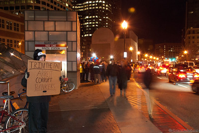 A sole protestor at Occupy Boston with her sign out on her own.