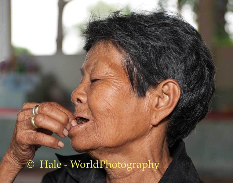 Lao Loum Woman Places Betelnut Plug in her Mouth