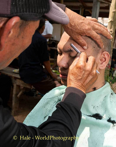 An Uncle Shaves Off His Nephew's Eyebrows As Part of Lao Loum Funeral Ritual