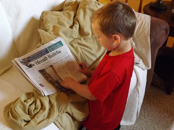 Eli Coxe using the morning paper to find words he knows to read to us.<br /> <br /> Photographer's Name: J.R. Rosencrans<br /> Photographer's City and State: Alexandria, Ind.