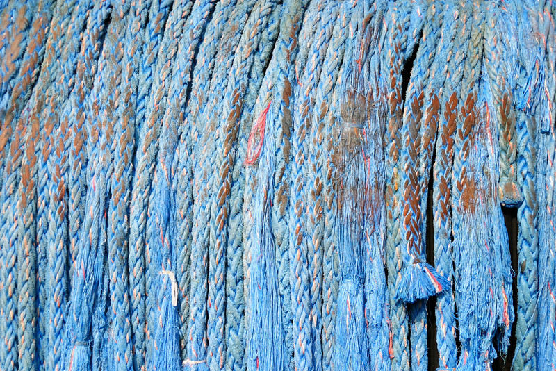 An arrangement of thick ropes draped over the stern of a tugboat form a blue background.