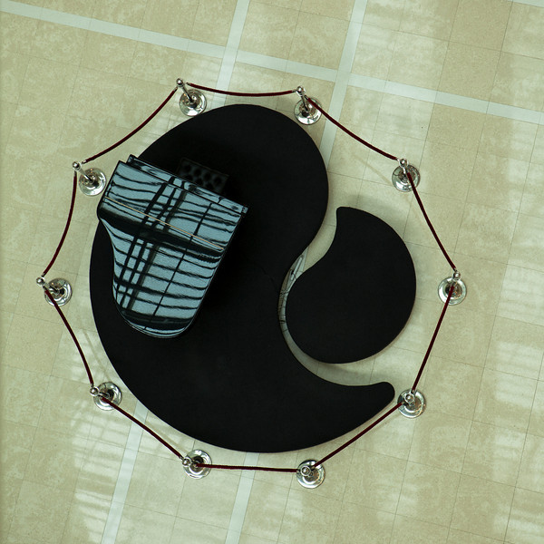 A piano in a shopping mall is located on a podium platform that is formed in the shape of yin yang symbol.