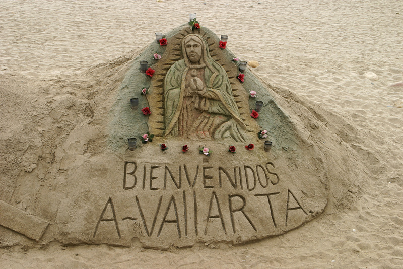 A colored sand sculpture of the Jesus on a beach in Mexico. This form of sand castle is very creative.