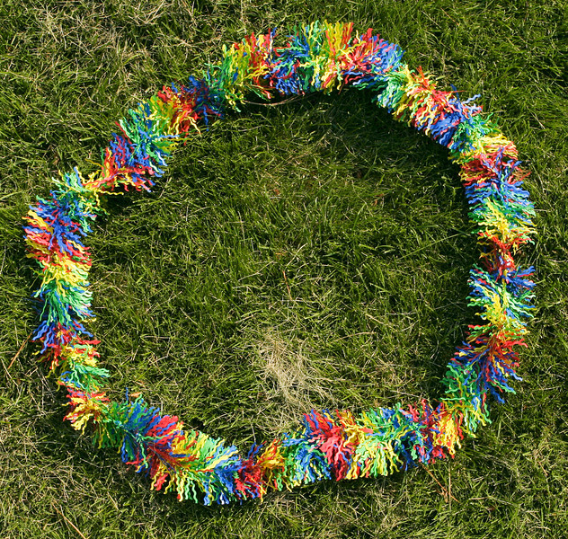 A colorful Hawaiian lei, laid down on thick grass is shaped like the letter O.