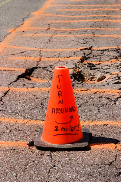 An orange cone and painted concrete warn of a set of cracks in the tarmac at an airport.