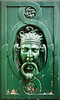 An old-style knocker in Paris on a door with weathered paint peeling. The fantastical image of the man holding the wrought iron ring in his mouth evinces the pain in the image.