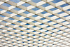 A white geometric ironwork lattice is an architectural abstract pattern when outlined against the sky.