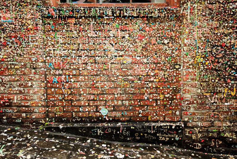 An old brick wall in Post Alley in the Pike Place Market in Seattle is covered with chewing gum deposited over a number of years. The gum is worked into names and other forms of graffiti.