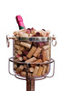 "A bottle of champagne with a bright pink foil label""chilling"" in an ice bucket filled with corks pulled from a variety of bottles. This is a festive image for parties, celebrations, and other happy occasions. This image is isolated to a white background."