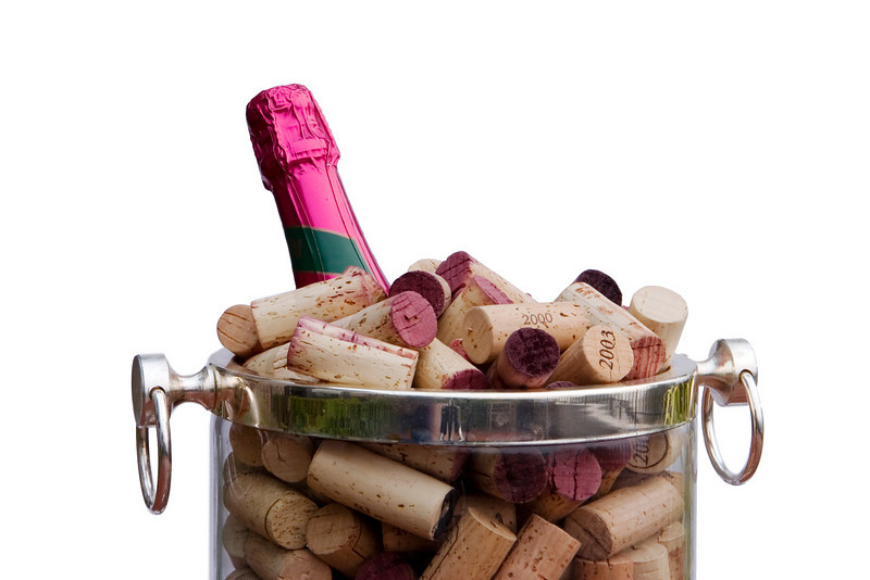 Detail view of a champagne bottle with a pink foil label in an ice bucket filled with corks pulled from many bottles. This is a festive image for parties, celebrations, and other happy occasions. Isolated to a white background.