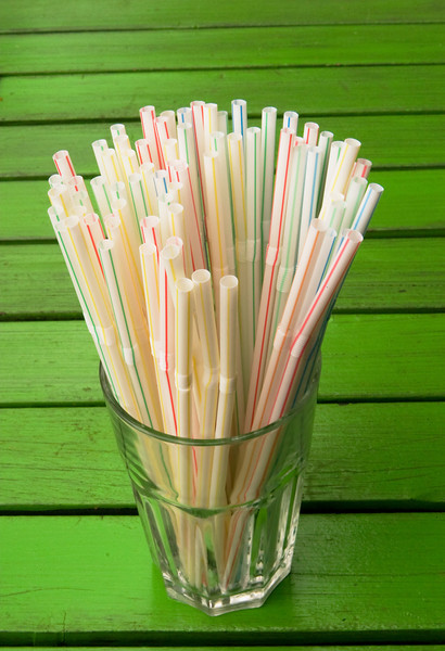 A water glass full of straws is on a bright green table.