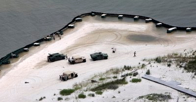 Alabama National Guard troops check an oil barrier along the beach in Gulf Shores, Ala., Saturday, June 5, 2010. Oil from the Deepwater Horizon disaster has started washing ashore on the Alabama and Florida coast beaches. (AP Photo/Dave Martin)