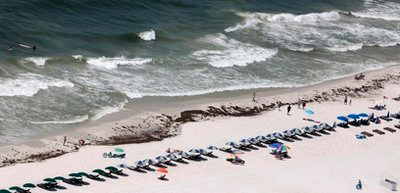 People walk near the dark brown stain of beached oil in Gulf Shores, Ala., Saturday, June 5, 2010. Oil from the Deepwater Horizon disaster has started washing ashore on the Alabama and Florida coast beaches. (AP Photo/Dave Martin)