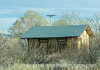 An old, abandoned railway depot spotted along a road in New Mexico.  Shot from a moving car.