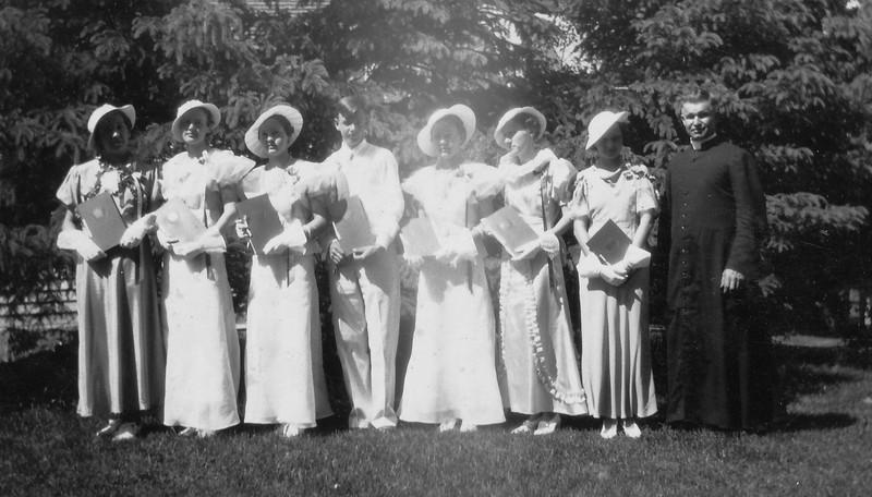 L to R: Ramona Conniff Jones, Marguerite Von Arx, Bernice Langen Bernstorf, Francis Welsh, Bernadette Langen Bisen, Irene Morman Heglaud, and Mary Morman Samb and on right end Father Wermerskirchen.