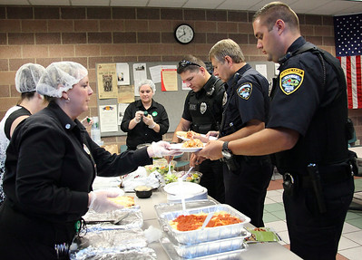 Sandra Anderson (left) of Elyria Olive Garden, serves lunch to police officers from left to right: Off. Ligas, Off. Cooley, and Off. Taylor. Lisa Mutnansky opens the salad dressing in the background. photo by Ray Riedel