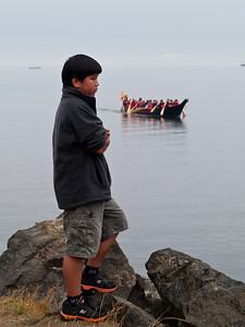 Native American boy watching the arrival of tribal canoes, Port Angeles, Washington, 2011.
