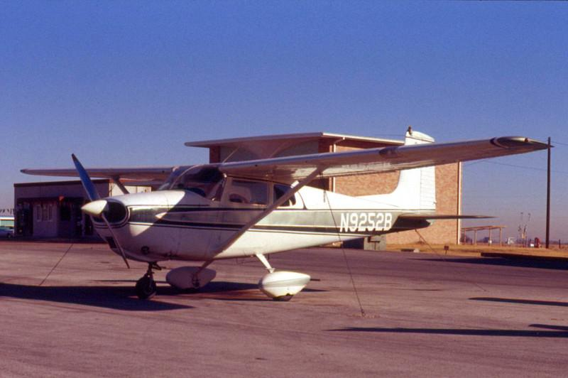 """CESSNA 175 SOLO PLANE<br /> Grand Prairie Airport, Grand Prairie, Texas<br /> <br /> An extremely personal airplane for me -- the one in which I performed my first solo flight. It was June 22, 1969, an extremely blustery day with winds out of the southwest at 20mph, gusting to 30mph. My flight instructor, Carl Frenzel, and I had just completed the day's lessons in turns and eights around a pylon, and had headed back for the airport. The wind was a quartering crosswind, which didn't present too much of a problem, and we taxiied back to the ramp for what I thought was the end of the lesson. Suddenly, Carl said, """"Hey, drop me off at the terminal. I need a Coke."""" Okay, I thought. Sure. I taxiied over to the terminal, Carl opened his door and got out, and said, """"Okay, take her around the patch a few times. Gimme three touch-and-goes."""" Huh? As the full impact of what he was suggesting hit me, I calmly said, """"Sure,"""" and taxiied back out to the end of the runway. I gave her the gas, crabbed a bit to the right for the crosswind, and we were off. Turning right prior to entering onto the downwind leg, I happened to look over and saw the right seat was empty. Holy cow! I was on my own!!! It was just me and the airplane and I was doing just fine. Turning onto final approach, I could feel the airplane was a little light, but no problem. I flared out over the numbers and chirp!, we were down. Two more times around """"the patch"""" and I taxiied up to the terminal to pick up Carl. """"Nice job!"""" he said. """"Thanks,"""" was all I could muster. Somewhat bemused by my calm approach to the current event, he said, """"You know, there was a guy in there asking 'What kid of fool would be out flying on a day like this?' I told him, 'That's my student, and I just let him go.' His jaw dropped down to his belt buckle and he ran right out and jumped in his own plane and took off."""" I was stunned -- more so than when he'd gotten out of the plane and kicked me out of the nest. That is indeed one day I'll remembe"""