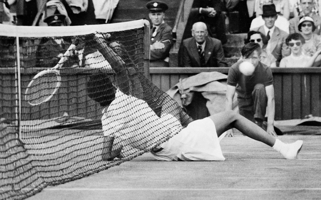 . Althea Gibson, of New York City, slides under the net to return the ball during semi-finals of the women\'s doubles at the All-England Lawn Tennis Club in Wimbledon, England, July 6, 1956.  Britain\'s Angela Buxton and Gibson defeated Louis Brough, of Beverly Hills, Ca., and Shirley Fry of St. Petersburg, Fla., 7-5, 6-4.  (AP Photo)