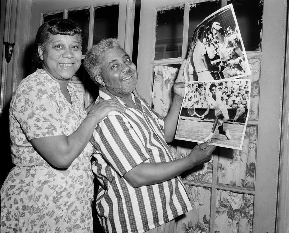 """. Daniel Gibson and his wife Annie beam at their home in New York as they hold AP RadioPhotos showing their daughter Althea at Wimbledon, England, where she won the women\'s tennis championship, July 6, 1957. Mrs. Gibson said \""""We\'re so proud of her we don\'t know what to say.\"""" (AP Photo/Harry Harris)"""